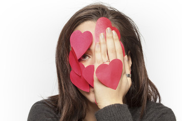 Exasperated girl with face covered with paper hearts