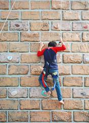 a kid climbs up a wall