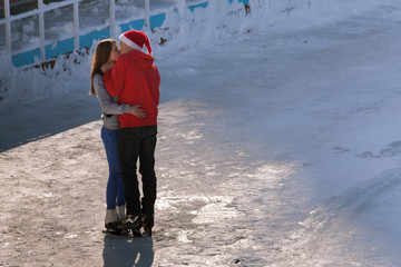 kissing teen couple at ice rink