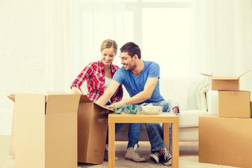 smiling couple unpacking kitchenware