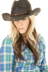 cowgirl in blue shirt and black hat close looking down