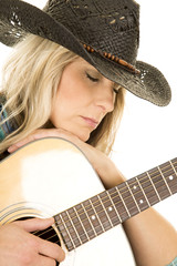 cowgirl with guitar in blue shirt close eyes closed