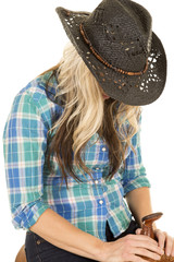cowgirl in blue shirt black hat head down