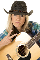 cowgirl with guitar in blue shirt close peace sign
