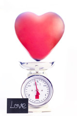Red heart shape balloon is weighted on scale. Love concept