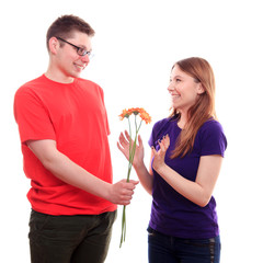The boy gives flowers to a girl