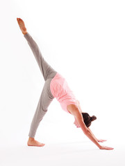 Young woman doing a yoga posture on a white background