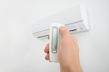 Man Holding Air Conditioner Remote Control