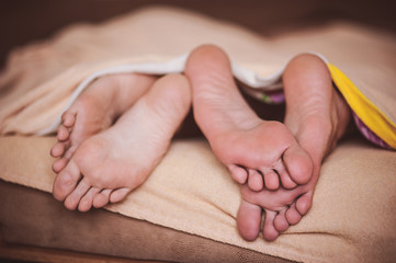 couple barefoot in bed no face