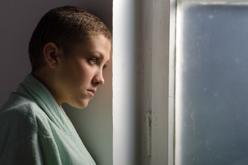 Young cancer patient standing in front of hospital window