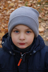 The boy in a cap and jacket for a walk in the park