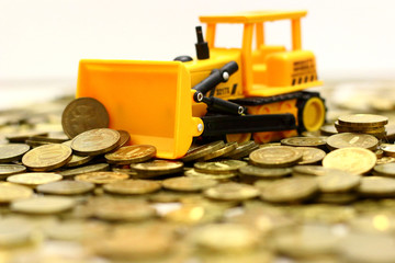 yellow toy bulldozer rakes rubles