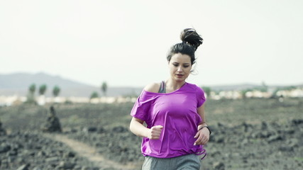 Woman with smartwatch and man jogging on desert, slow motion