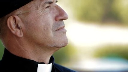 Old pastor wearing a black shirt and clerical collar