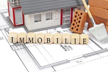 Bauplan mit Ziegelstein und Haus mit Immobilie
