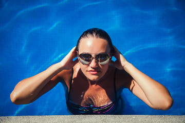 portrait of a beautiful brunette posing in the pool