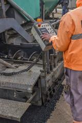 Asphalt worker hand controling paver machine