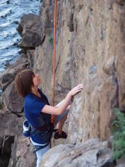 Girl climbing up a cliff.