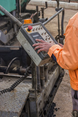 Asphalt worker hands controling paver machine
