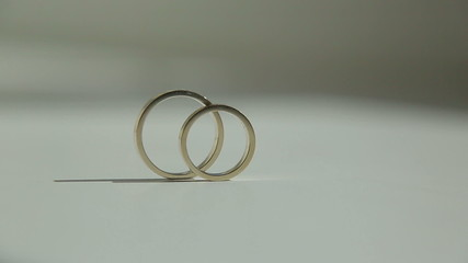 Wedding rings rolling out of the frame