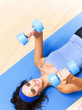 Woman exercising with dumbbells, indoor
