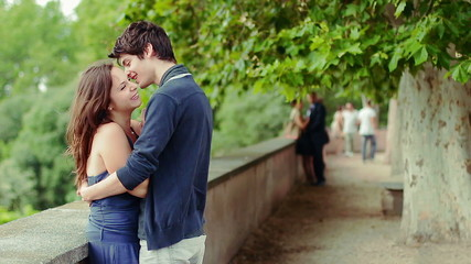 man kissing young woman , there is a mature couple in love in background