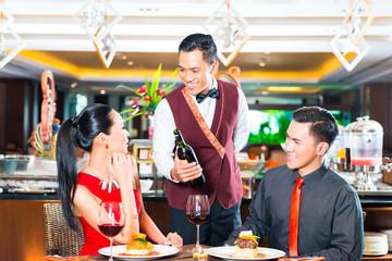 Waiter serving wine in Asian restaurant