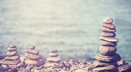 Vintage retro hipster style image of stones on beach, spa concep