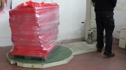 industrial machines puts transparent palstic film on pallets