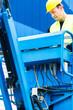 Kranfahrer fährt hydraulische Hebebühne über Schaltpult