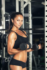 Young woman lifting the dumbbells in the gym