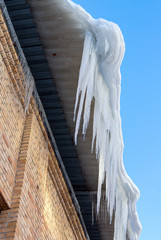 Large icicles hanging on the roof of the house in springtime