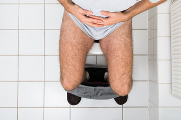 Man In Toilet Suffering From Stomachache