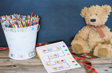 Bucket of pencils, old bear and  coloring book