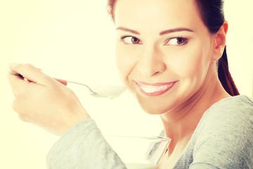 Beautiful woman eating yoghurt.