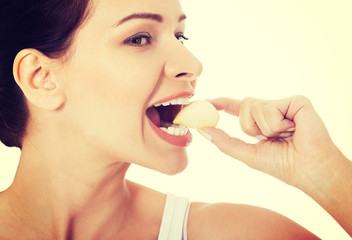 Beautiful woman eating garlic.
