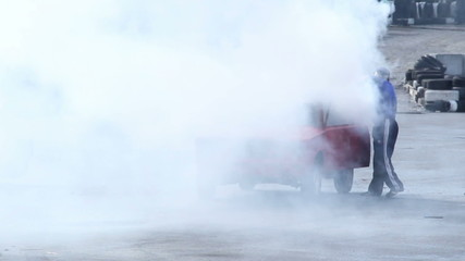 Man extinguishing car fire after crash, accident, thick smoke