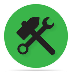 Hammer and wrench on a green background