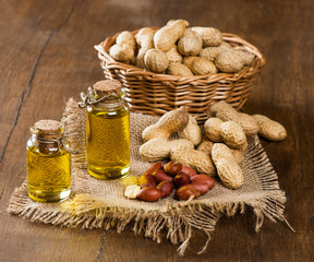 peanut oil and nuts on a wooden table