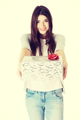 Young woman holding present with red bow.