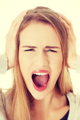 Beautiful woman screams and covers her ears.