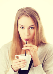Woman is drinking from a cup with a straw.