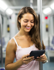 Woman with ereader in subway train