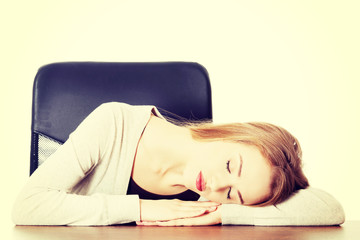 Young casual woman is sleeping on a desk.
