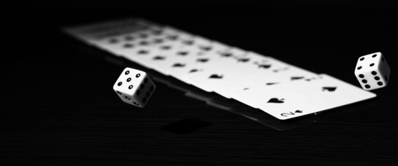 A gambler rolling the dice to win. on a reflective surface with