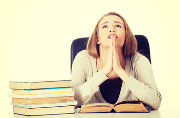 Student woman sitting by a desk and praying.