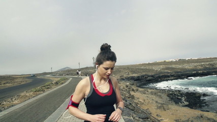 Young woman with smartwatch jogging by sea,