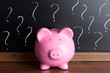 Piggy Bank With Question Mark On Black Board - 76599516