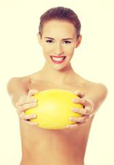 Beautiful woman holds yellow fresh melon.