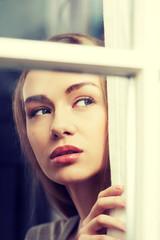 Beautiful woman is looking through window.
